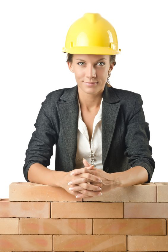 15926622 - young female builder near brick wall